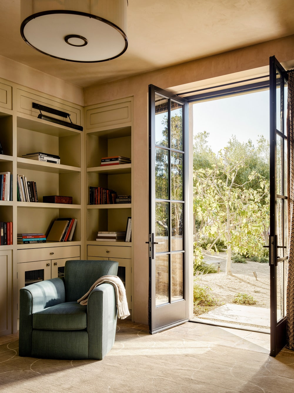 This corner of the lbrary has a dark gray armchair that stands out against the light wooden bookshelves of the wall. This stands on the side of the French glass doors that lead to the landscape outside.