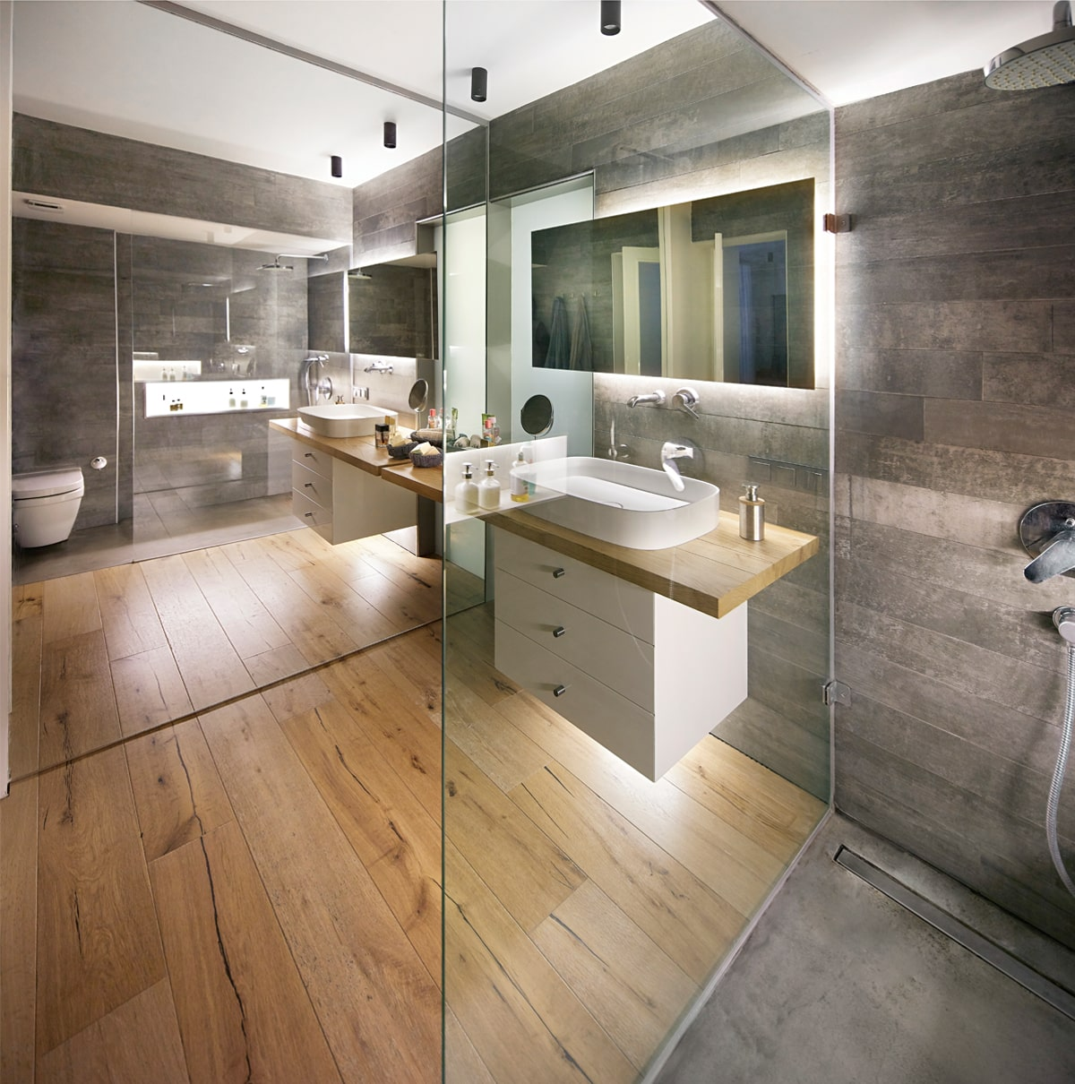 This other bathroom has a modern white floating vanity separated with glass walls from the toilet area and the shower area that has a gray floor.