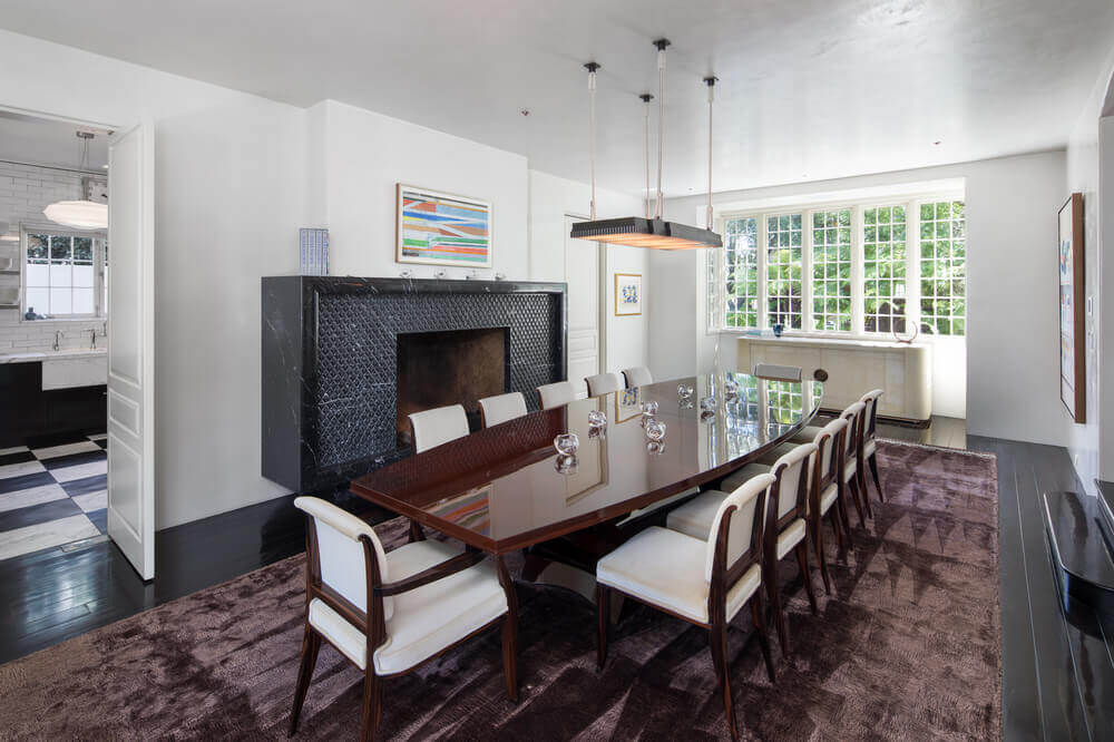 This is a formal dining room with a black flooring that blends well with the large black mantle of the fireplace. This stands out against the white walls and white ceiling that hangs a simple light over the sleek dining table.