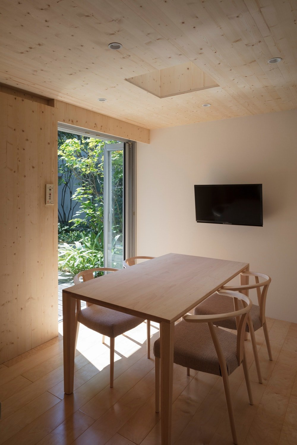 This is the informal dining area at the edge of the kitchen. It has its own sliding door that opens to the garden of the back and a wall-mounted TV.