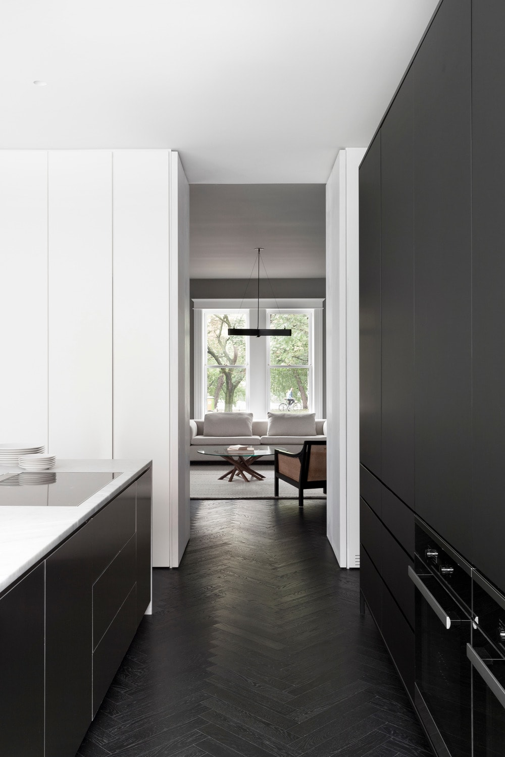 The kitchen has a direct access to the living room as can be seen on the far end of the long and narrow kitchen with black cabinetry and black flooring.