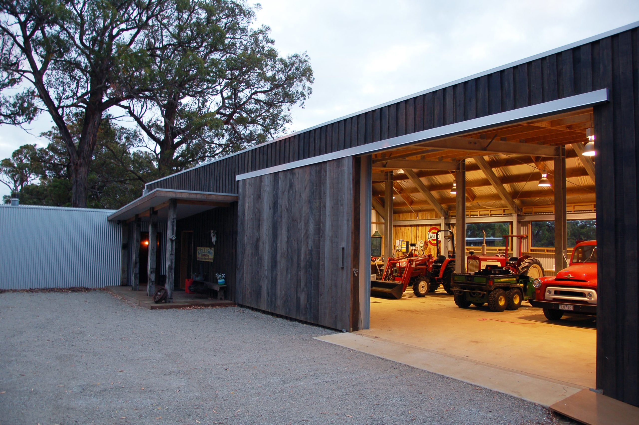 This close look at the large shed and garage showcases its beautiful wooden ceiling with exposed beams connected to pillars that separate the parking spaces for the vehicles.