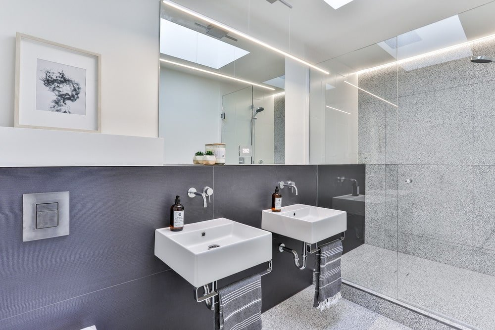 This bathroom has a couple of floating porcelain sinks on dark gray tiles of the wall that extends to the wall of the glass-enclosed shower area beside the sinks.