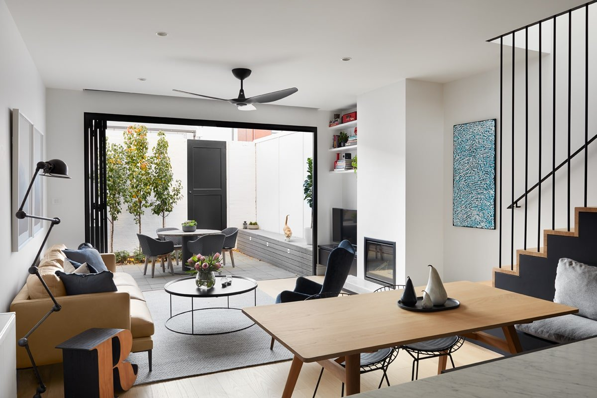 This is a view of the great room from the vantage of the kitchen. You can see here the dining area with a wooden dining table and the living room illuminated by the large open wall leading to the patio.