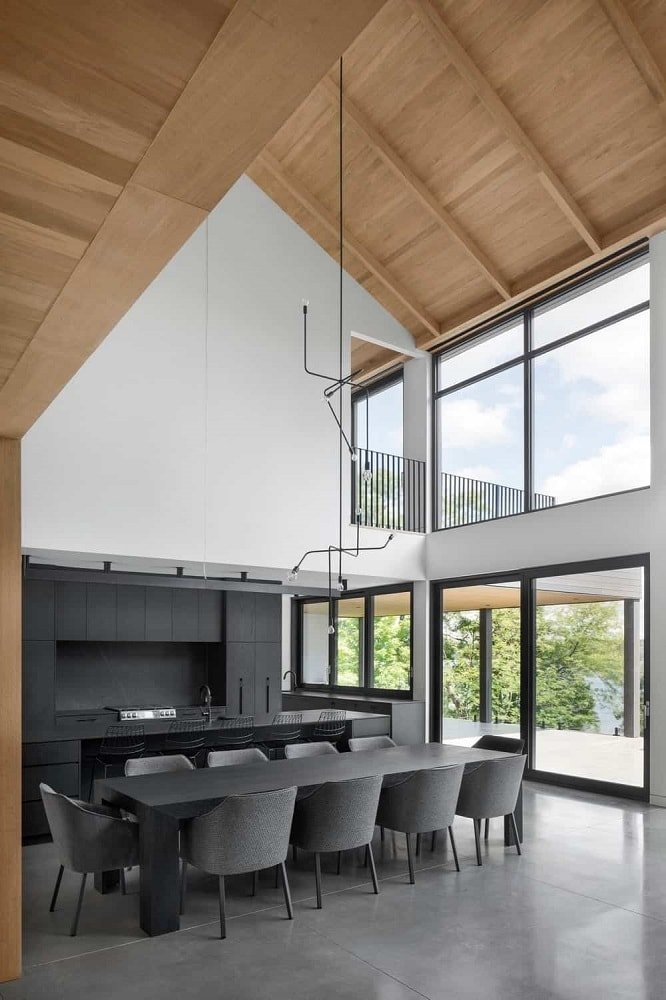 This is the gorgeous great room that houses the kitchen and dining area. It has tall white walls along with glass walls. This brings a brightness to the black dining table surrounded by black cushioned chairs.
