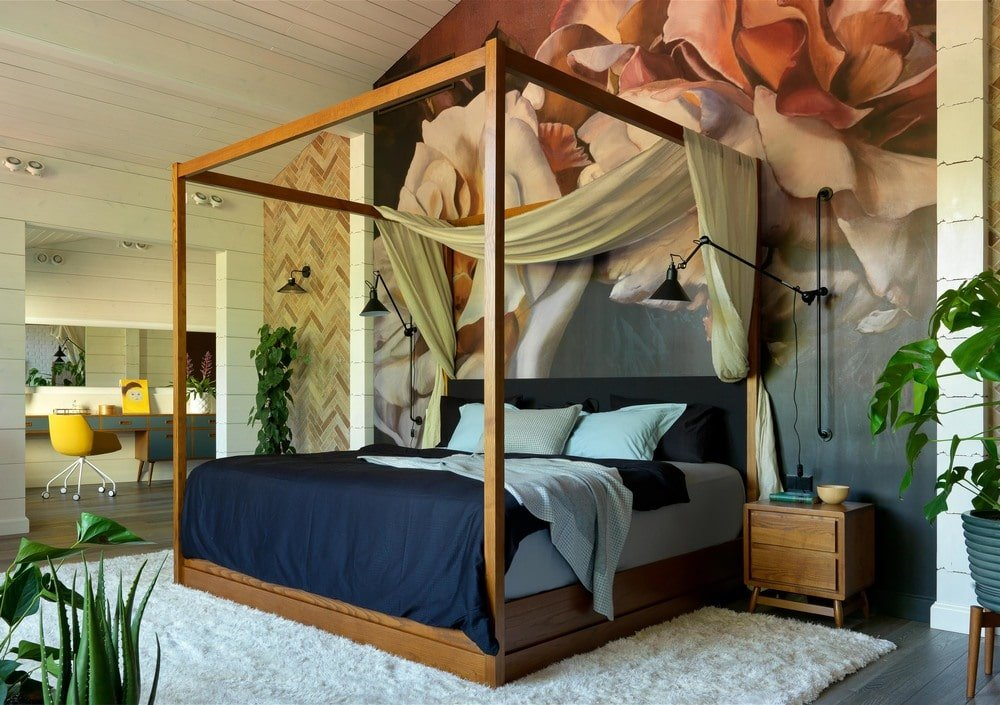 The primary bedroom of the house has a charming wooden four-poster bed adorned by its navy blue sheet and contrasting white pillows. This matches well with the large area rug on the floor underneath the bed.