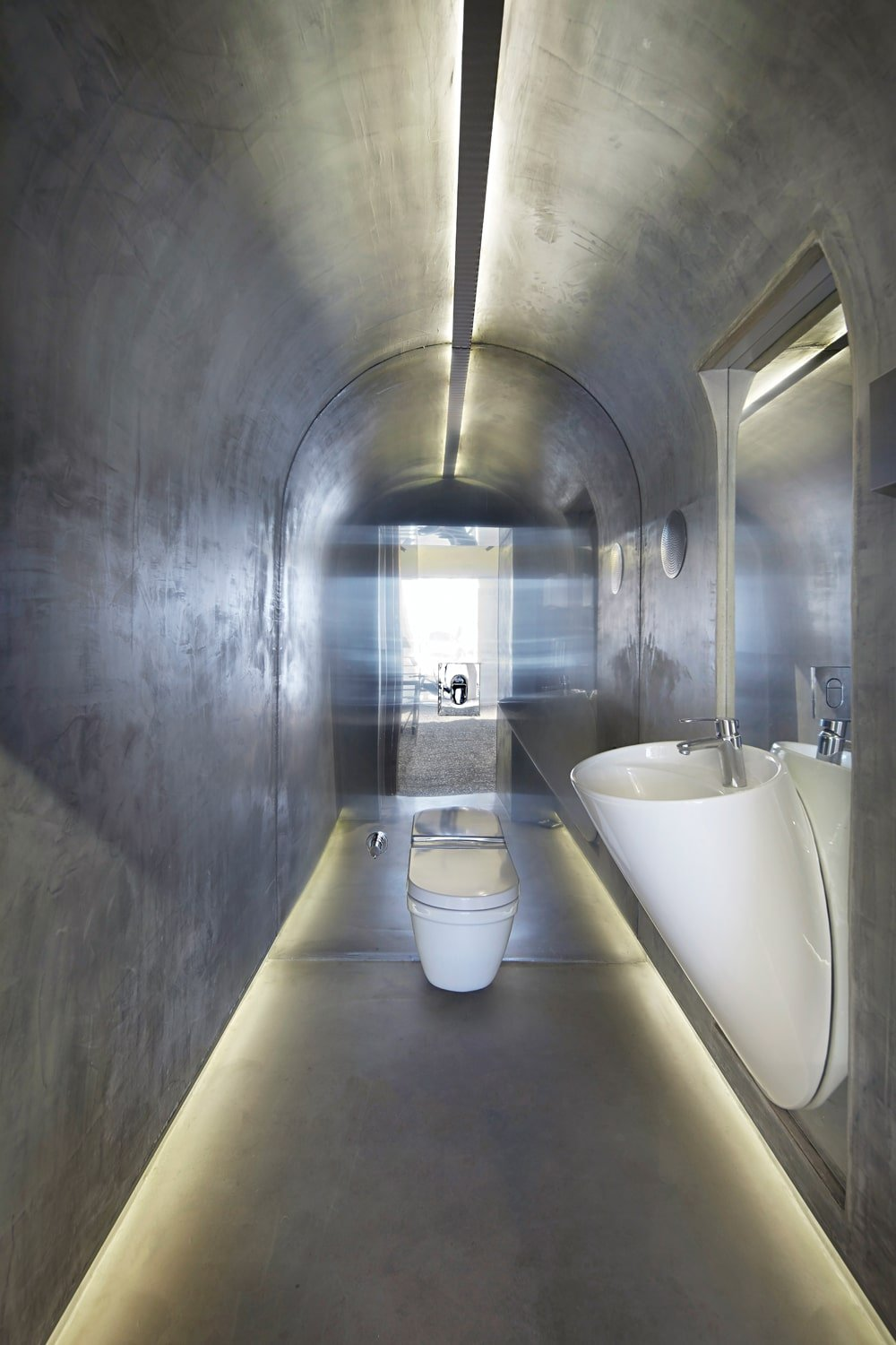 The small bathroom is augmented by the mirror wall to make it appear bigger than it actually is. This has gray walls that blend with the cove ceiling that makes the white porcelain sink and toilet stand out.