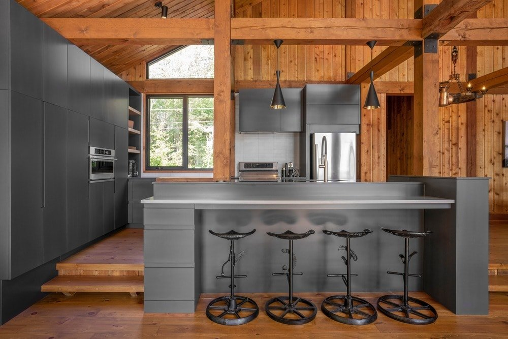 This kitchen has modern dark gray cabinetry to go well with the modern appliances. These are complemented by the exposed wooden beams of the tall ceiling that connects with the kitchen island through thick wooden columns.