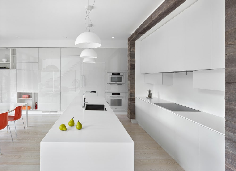 This is a beautiful white kitchen with a narrow and long design to its modern white cabinetry and white kitchen island. These are complemented by the light hardwood flooring and the white pendant lights over the kitchen island.