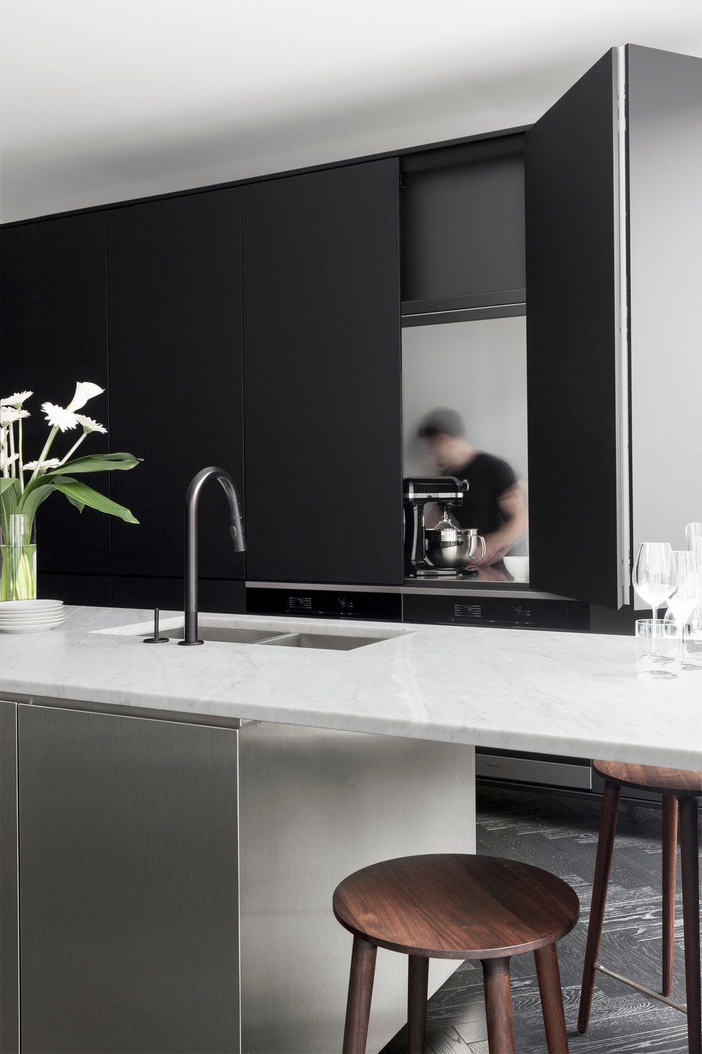 These black panels of the modern structure open up to reveal the work space of the kitchen for cooking. These panels fold in itself for an ingenious space-saver design.
