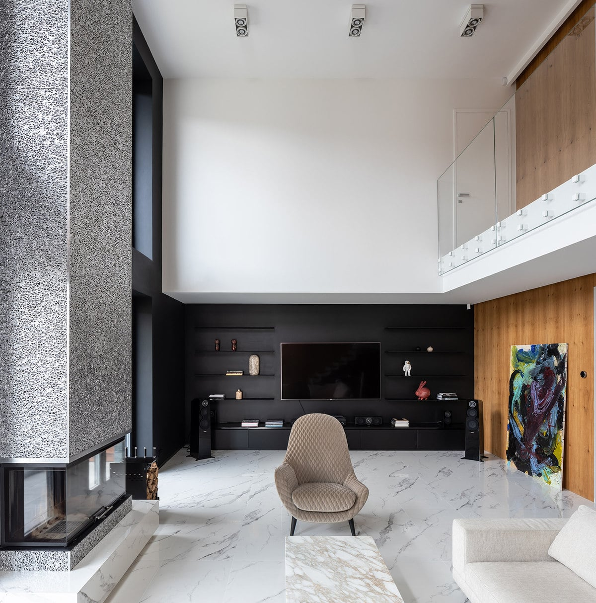 Behind the brown armchair is a large black wall with built in shelves that support the wall-mounted TV. There is also a large artwork leaning on the wall on the side.