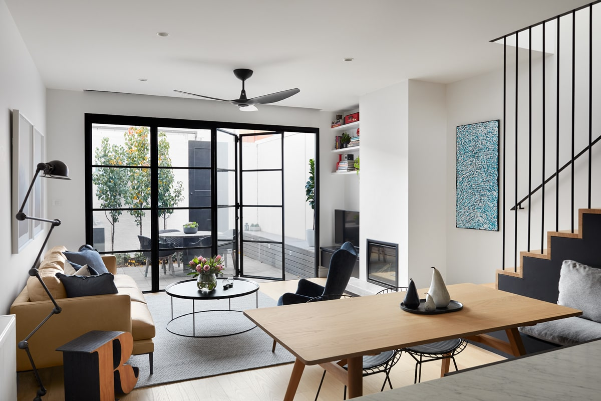 This large open wall that leads to the patio beyond can close and open with its folding set of glass doors with black frames that stand out against the bright walls and ceiling.