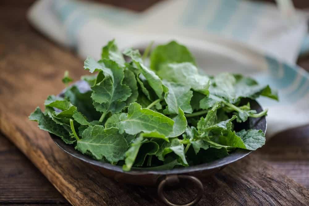 Baby kale leaves in a rustic bowl.
