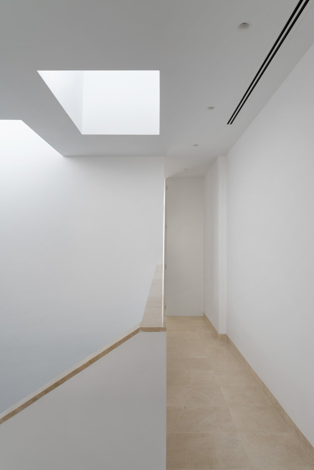 This is the second floor landing with a bright and white look to its ceiling that is augmented by the skylights that bring in natural lighting.