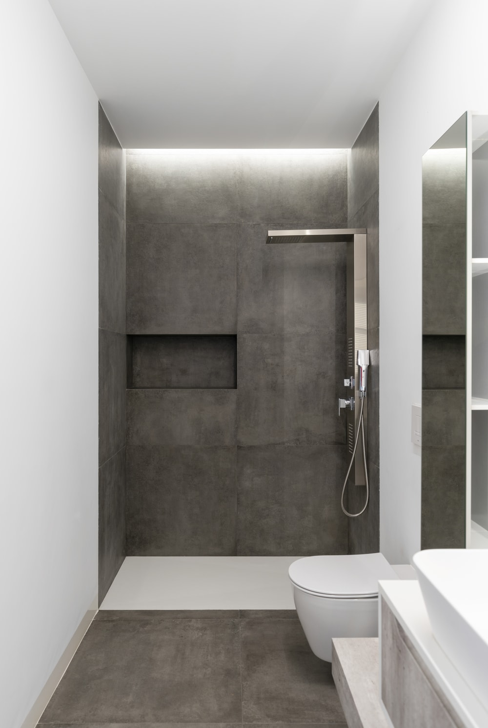 This is the walk-in shower area with modern fixtures and a dark gray wall on the far side.