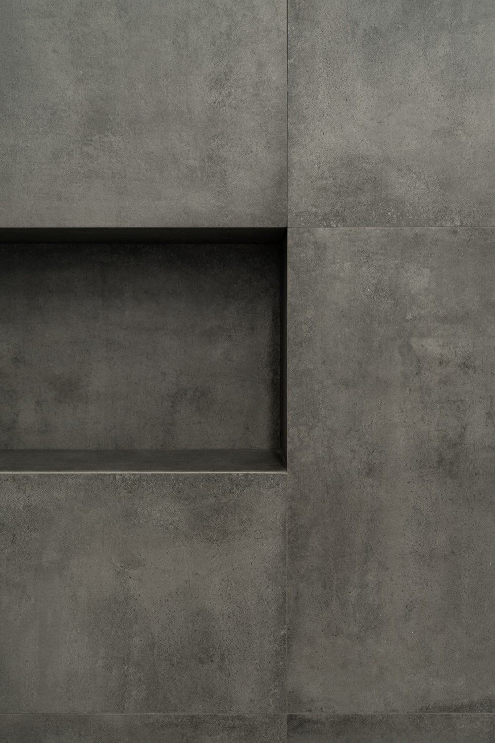 This is a close look at the dark gray wall of the shower area with an alcove for bath products.