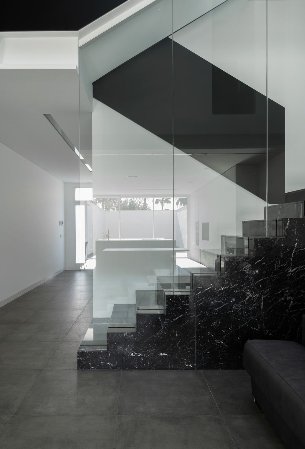 This is a closer look at the staircase that has black marble steps and a large glass wall that gives it a unique look.