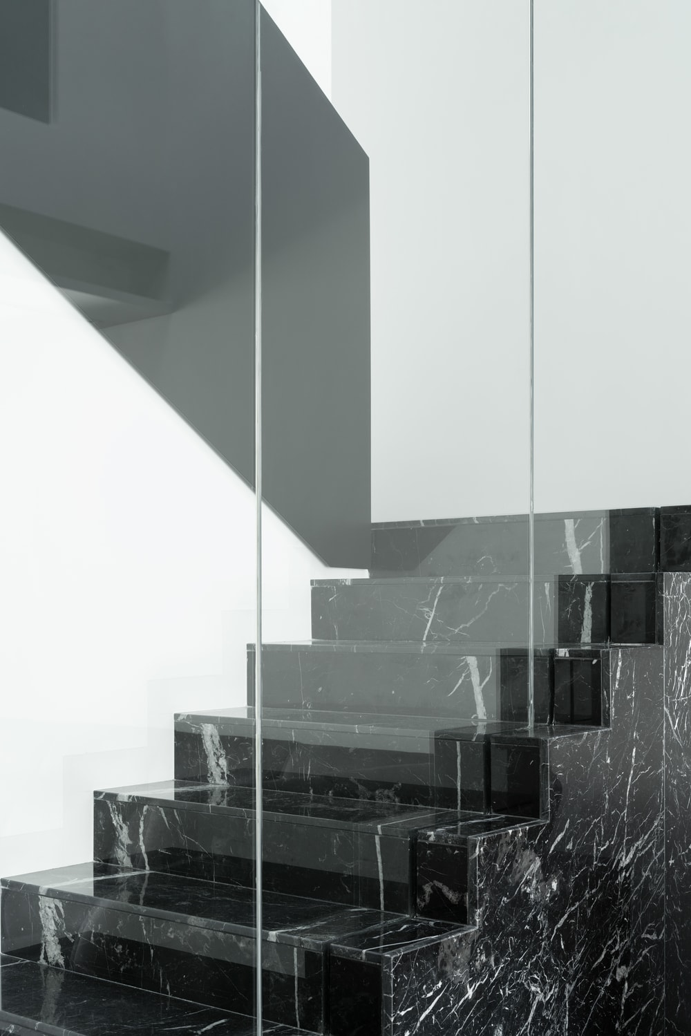 The black marble staircase stands out against the white walls and the glass wall.