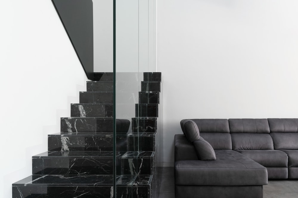 This angle showcases the dark gray sofa of the living room and the black marble steps of the staircase.