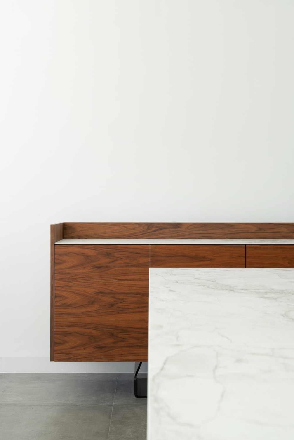 This is a close look at the white marble dining table with a wooden structure at the far end against the white wall.