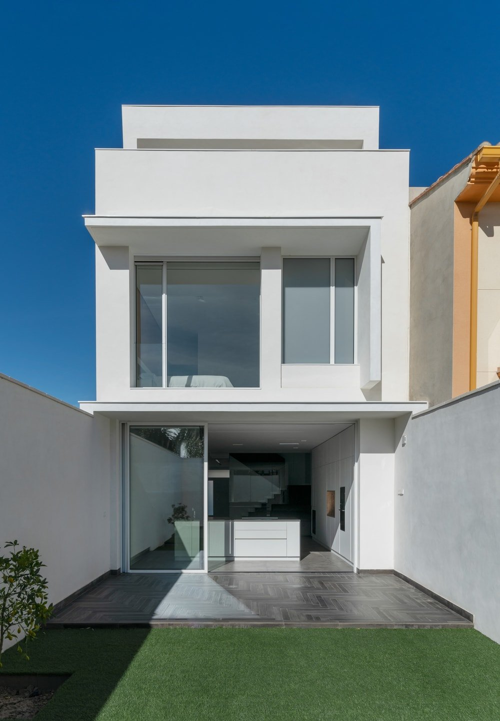 This back view of the house showcases the kitchen island at the ground level and the large balcony of the top floor.