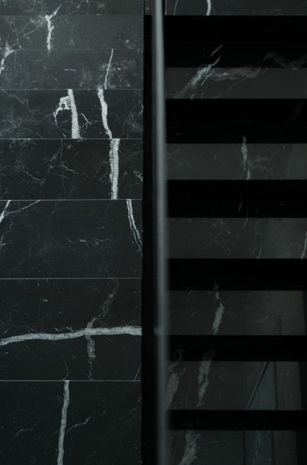 The combination of the glss wall and the black marble gives the staircase a unique decorative look.