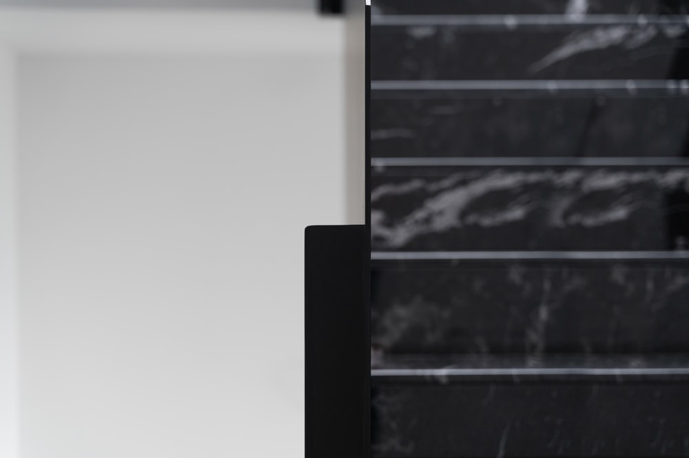 This is a close look at the black marble staircase with a thin black panel on the side for handles.