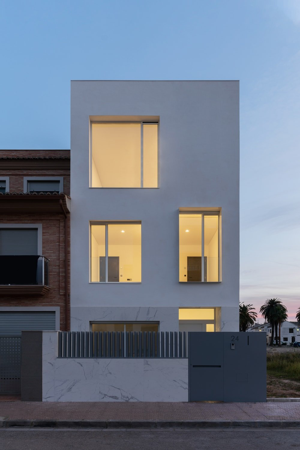 The large windows of the house glow warmly from the interior lights that also give a glimpse of the interior walls.