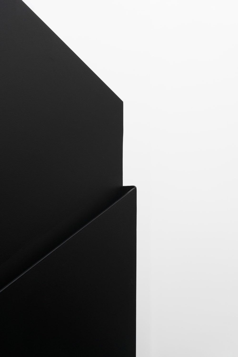 This is a close look at the side of the staircase with a thin black panel that serves as the handle of the stairs.