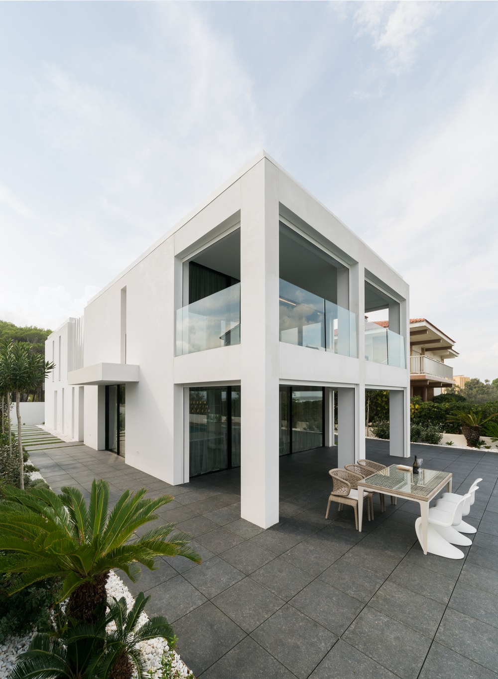 This look of the back of the house showcases the large balcony of the second level with glass railings for safety and aesthetics.