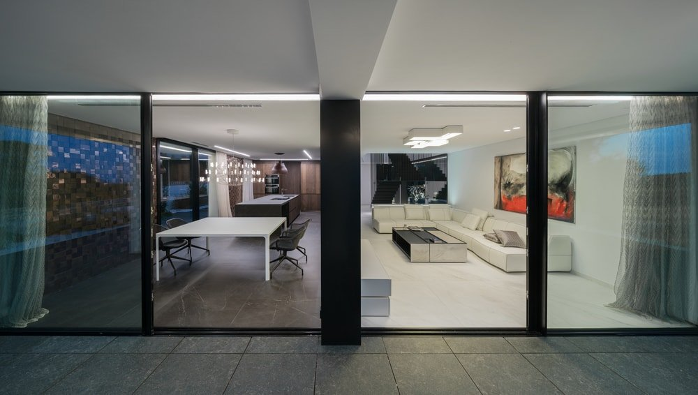 This is a view of the interiors from the outside. Here you can see the large living room on the right with a large sectional sofa. On the left side is the dining area and the kitchen on the far side.