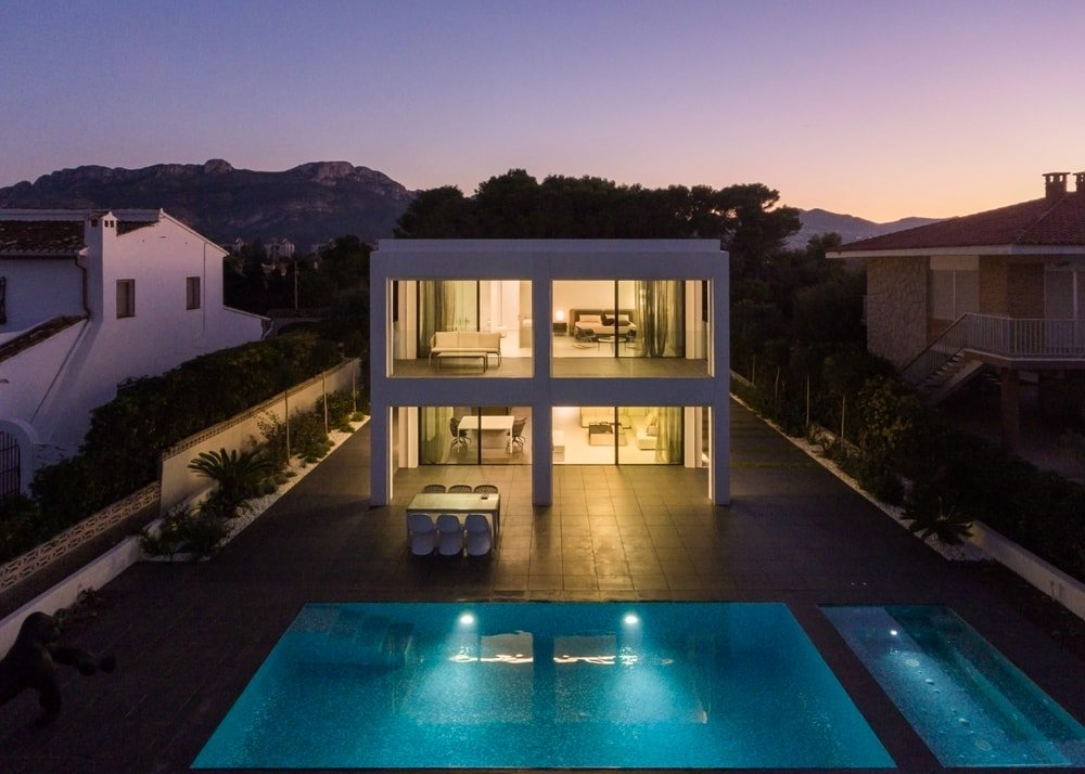 This aerial view of the house showcases the warm glow of the house from its glass walls and the ethereal glow of the pool from its own lighting that makes it stand out against the dark grounds.