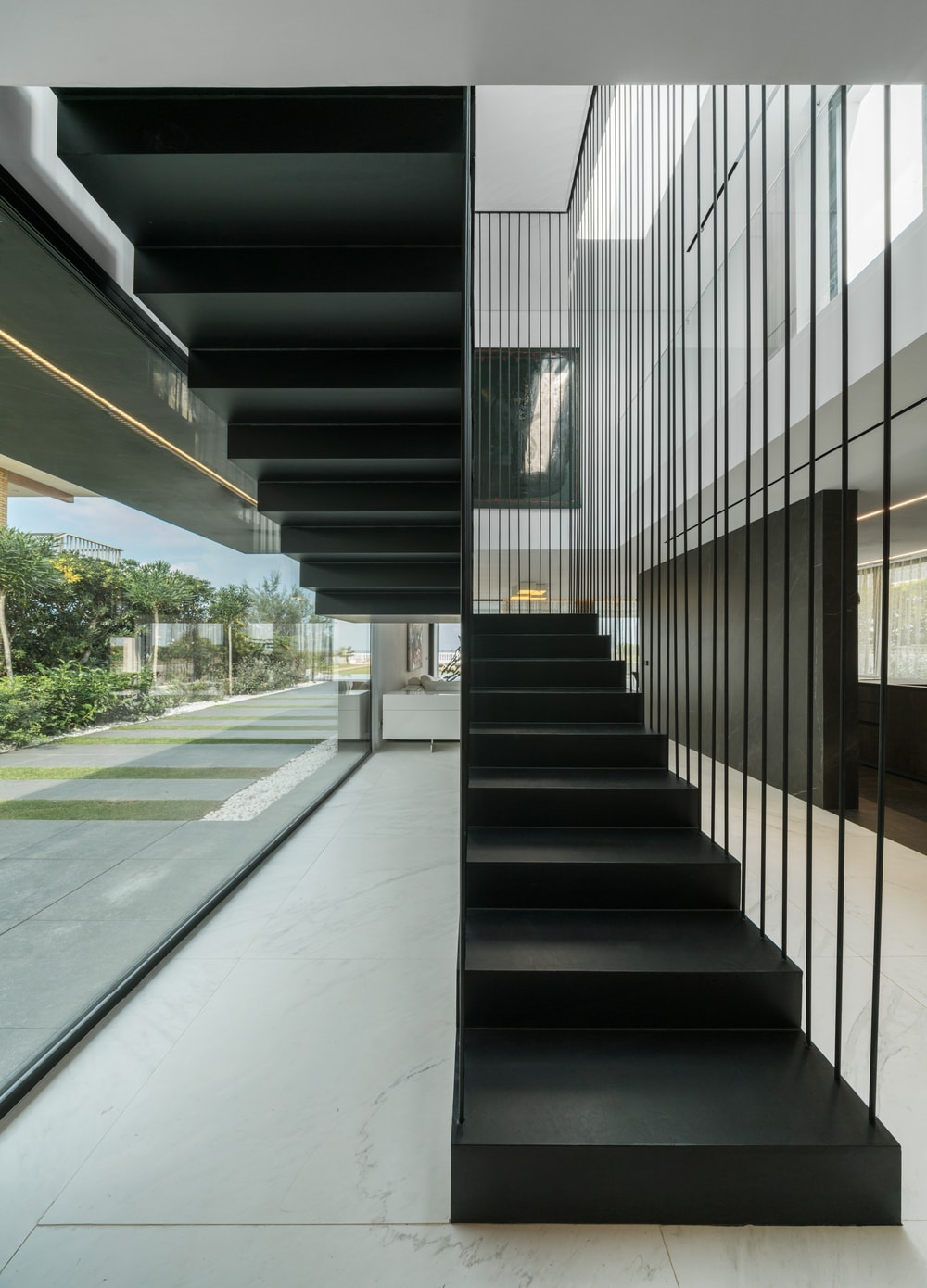 This is a close inspection of the modern staircase with a black tone to stand out against the bright elements of the area.