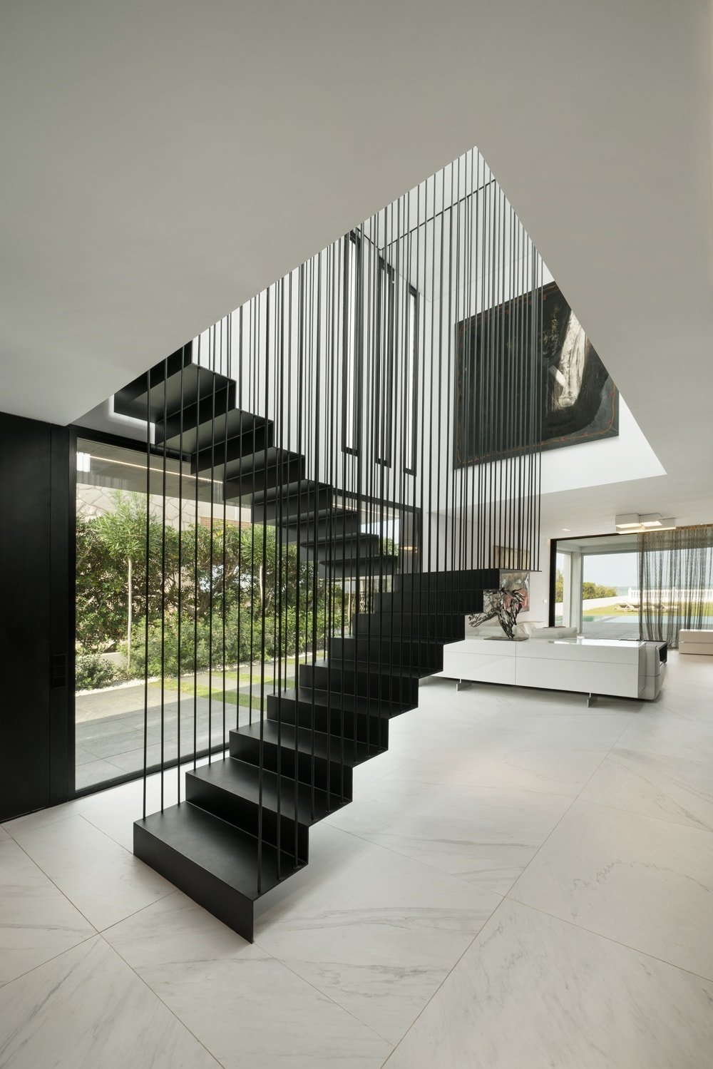 Upon entry of this beautiful home, you are welcomed by this simple yet astonishing foyer that has a modern black staircase that stands out against the white flooring tiles, white walls and white ceiling.