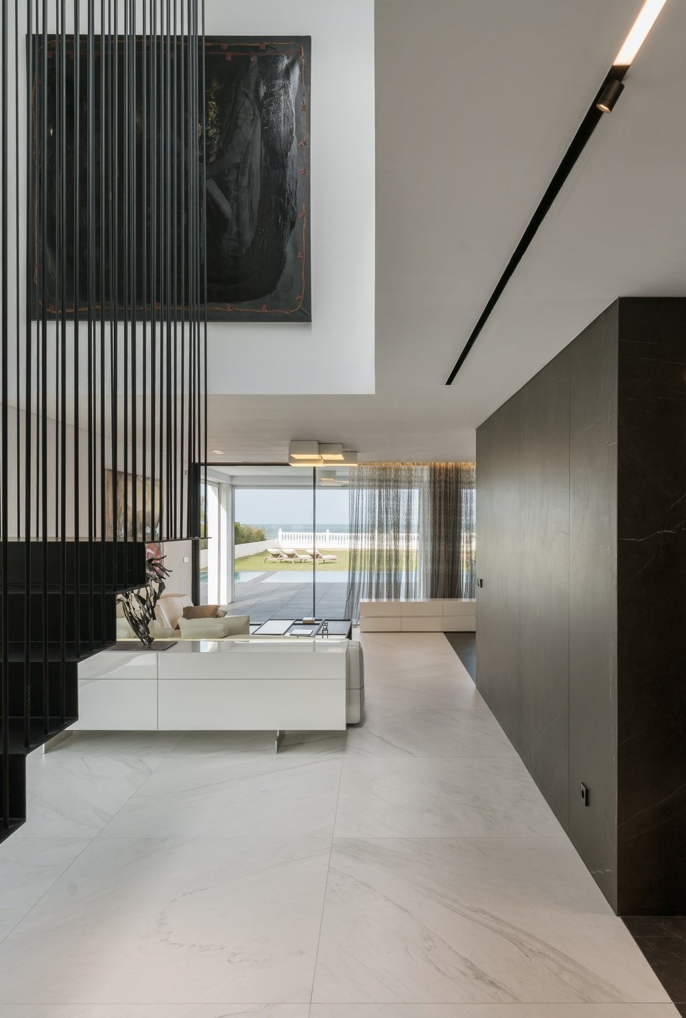 From the black modern staircase, you can clearly see the living room and its bright furniture contrasted by the black wall that separates it from the kitchen.