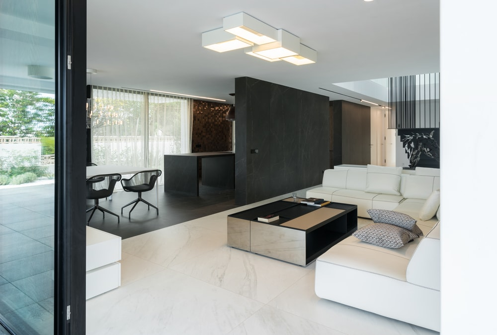 The light tone of the living room flooring tiles is contrasted by the dark flooring tiles of the dining room and kitchen to match the black walls.
