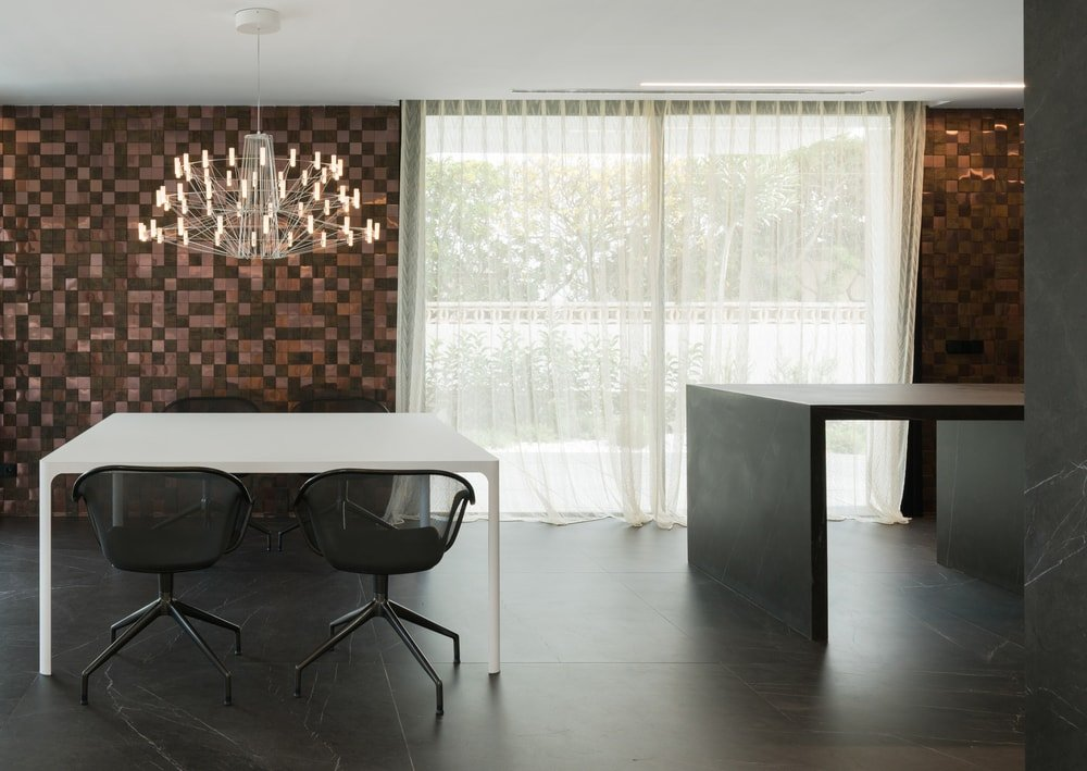Here is the lovely dining area beside the kitchen. It has a lovely white modern dining table paired with black chairs that blend with the black flooring. These are then topped with a decorative chandelier.