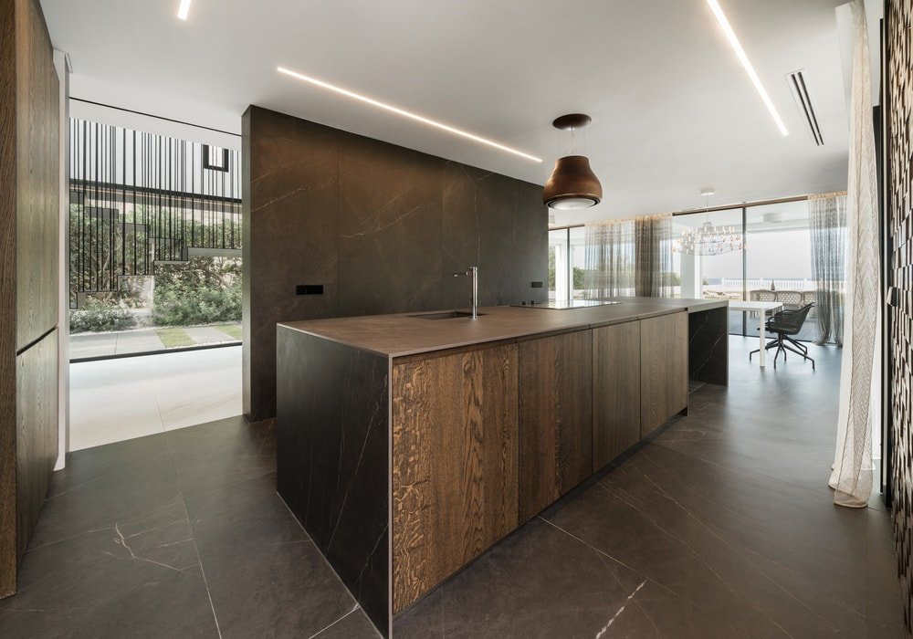 This view of the kitchen showcases its charming black and white tone. It has a large kitchen island that contributes to its long and narrow design.