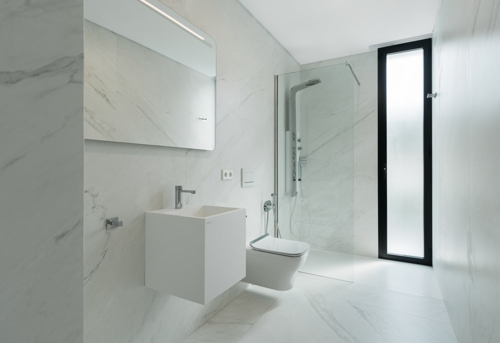 This is the modern bathroom with a white floating vanity beside the white floating toilet.