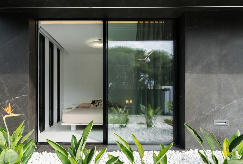 This is a look at the bedroom from the vantage of the miniature garden outside its glass doors. Here you are given a glimpse of the platform bed inside.