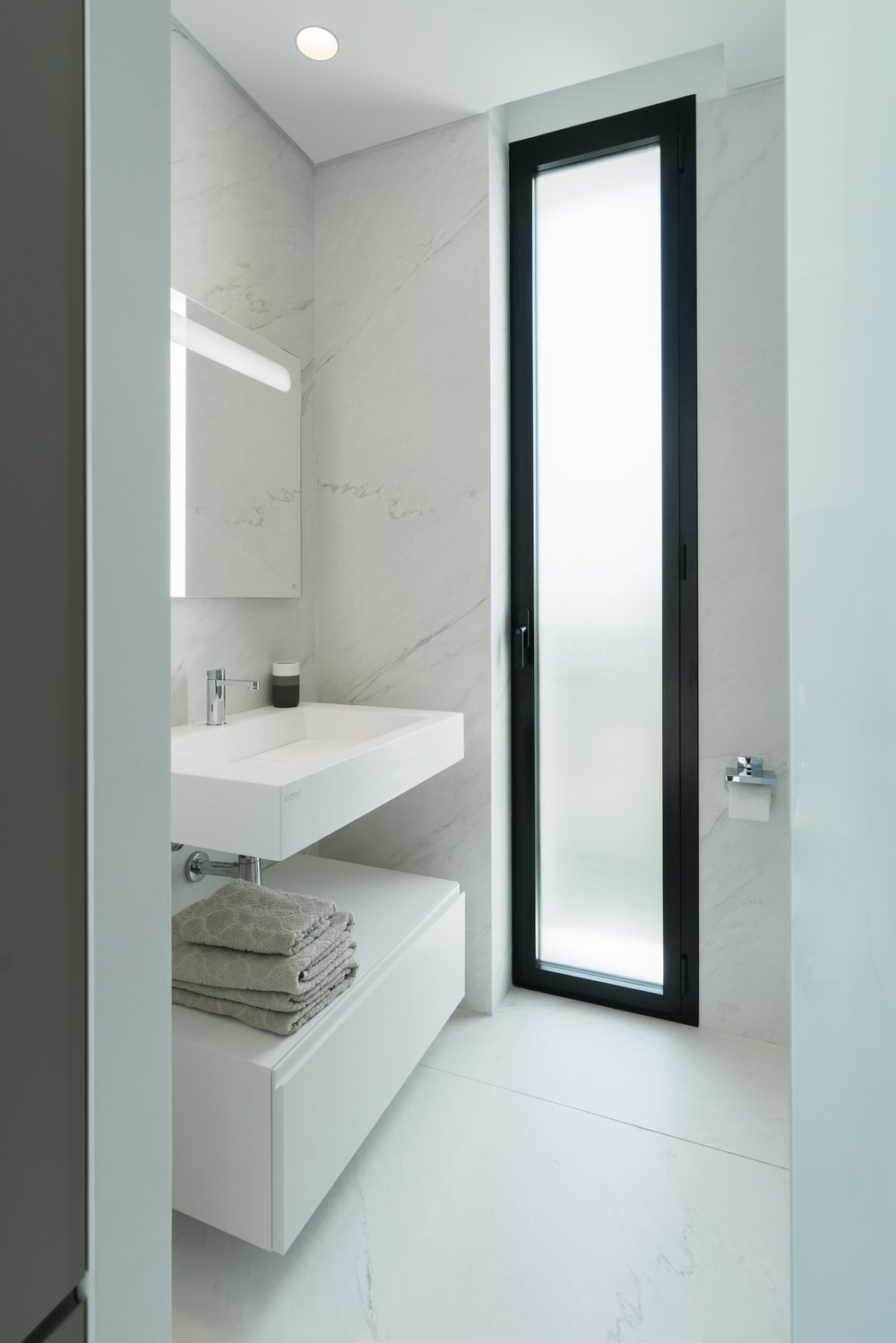 This other bathroom also has a white modern vanity that blends well with the white marble walls brightened further by the tall glass window.