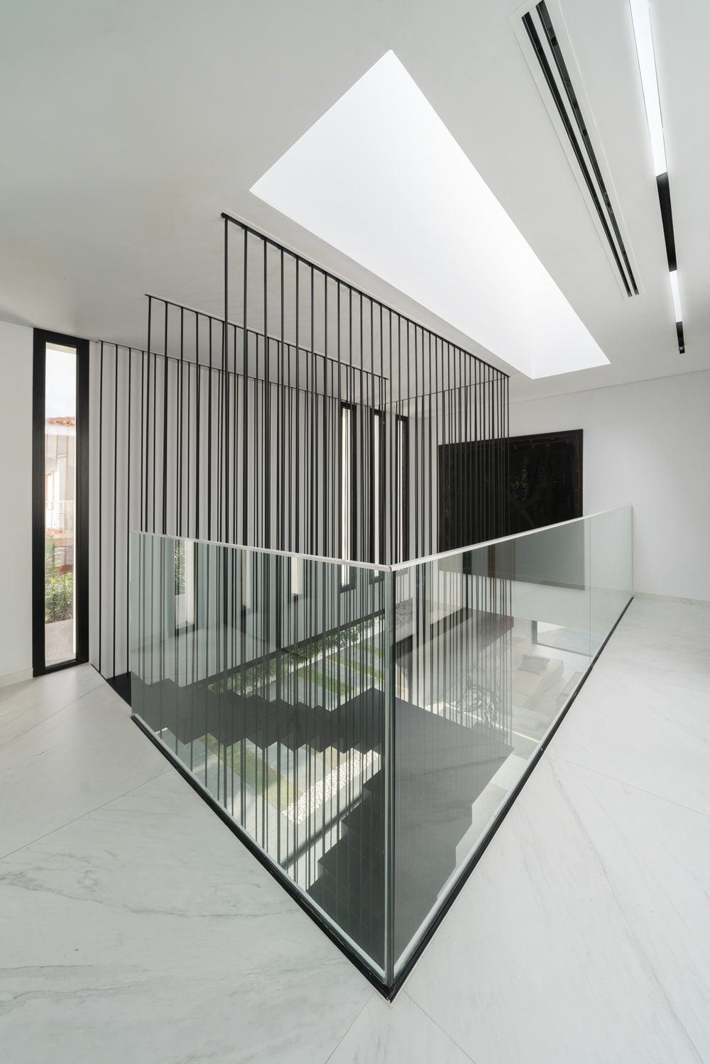 This angle showcases more of the glass railings of the indoor balcony. This allows for a bigger view of the staircase's tall ceiling.