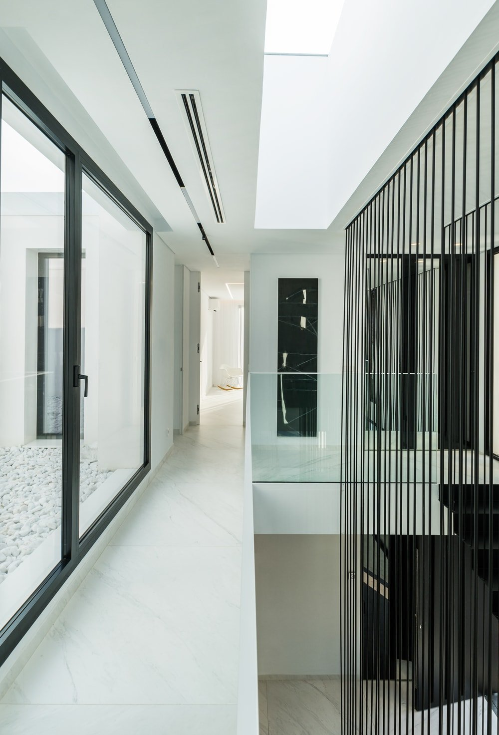 This is the second-floor hallway with a white marble floor and low glass walls on its indoor balcony that looks over the foyer and stairs.