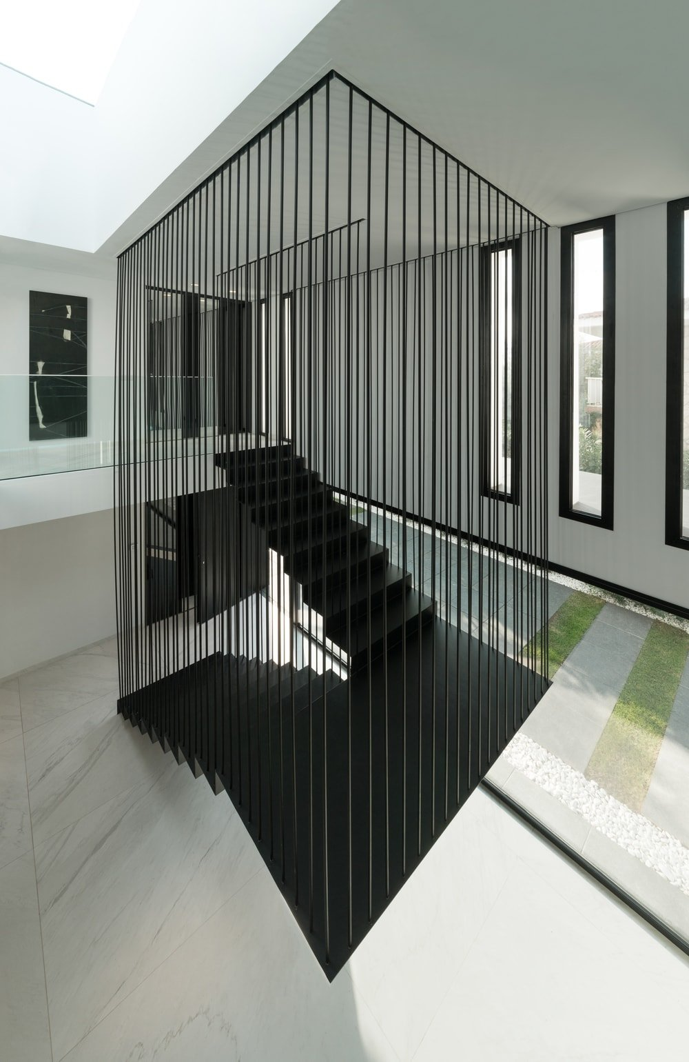 This is a view of the modern staircase from the vantage of the second-floor landing. This angle shows the contrasts of the staircase to the surrounding white elements.