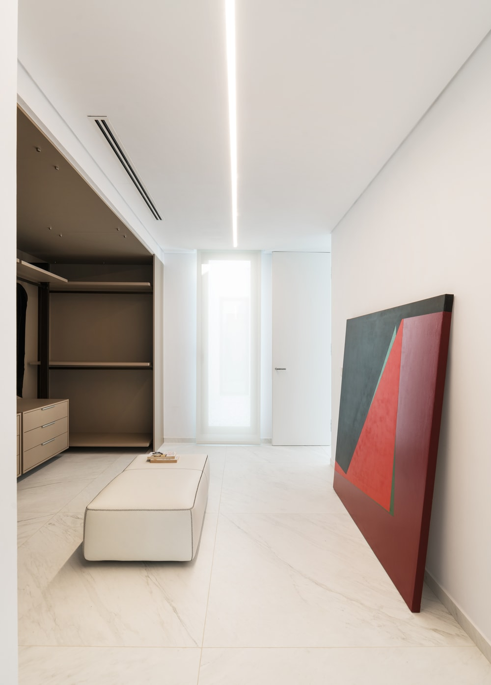 This is the walk-in closet of the house with built-in shelves and cabinetry as well as a cushioned white bench in the middle adorned by a large colorful painting.