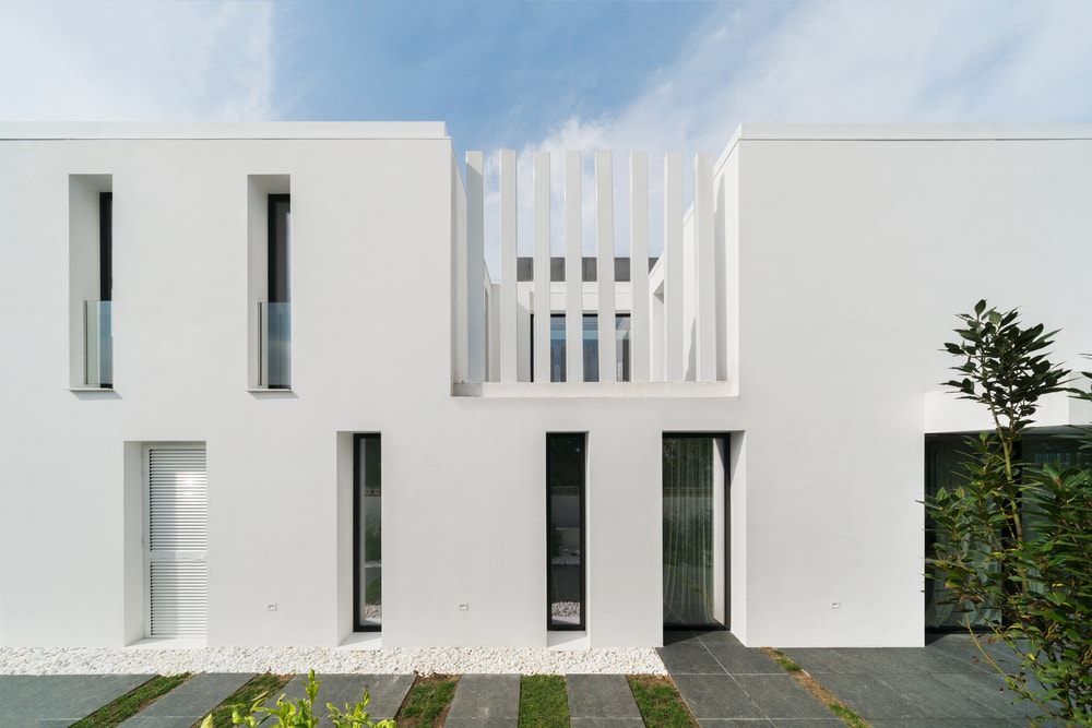 This is the front look at the house with bright white exterior walls adorned by the tall and thin windows.