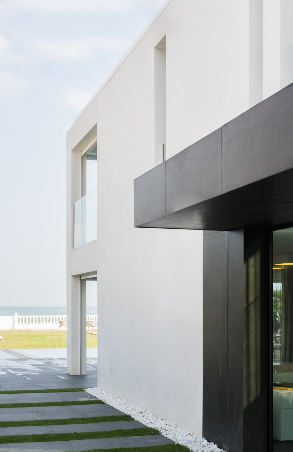 This angle of the main entrance shows the contrast of the dark exteriors to the white walls of the back section of the house.