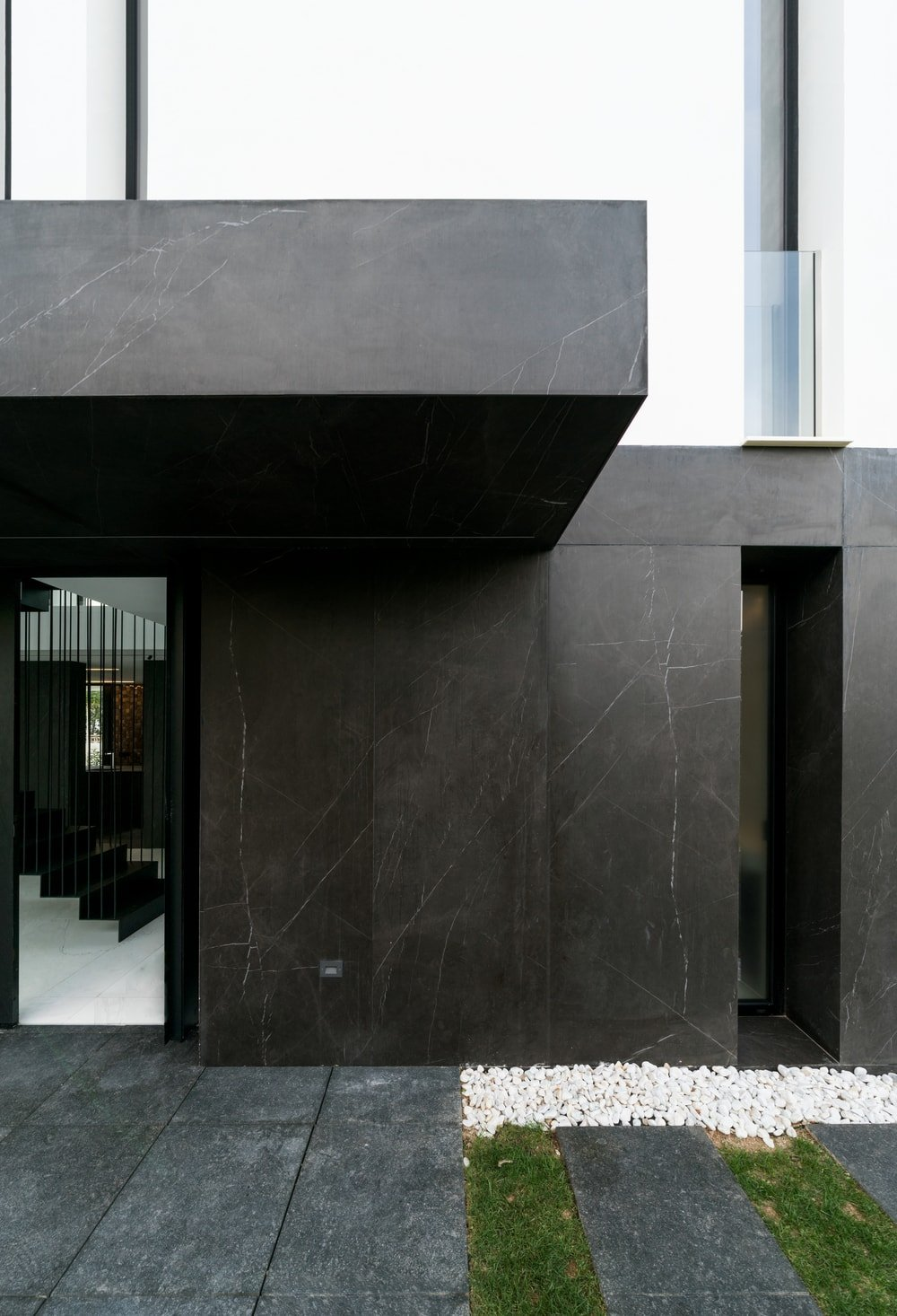 The black material used on the main entrance of the house extends to the sides that has a tall and thin window.