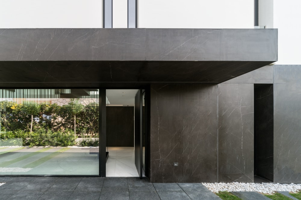 The main entrance has a glass door attached to a large glass wall that brings in natural lighting to the foyer.