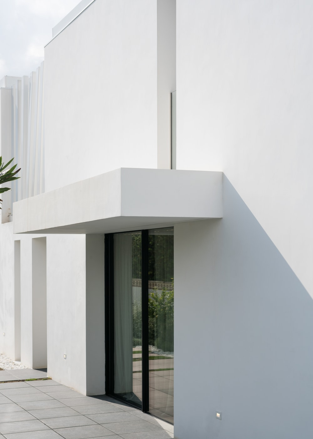 This is a look at the side entrance of the house with large glass sliding door to complement the white walls and white cover of the entrance.